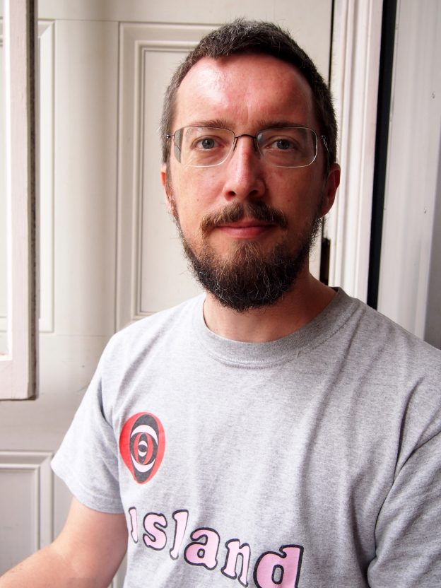 Bearded bespectacled man wearing a t-shirt