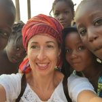 White woman in turban is surrounded by smiling African children