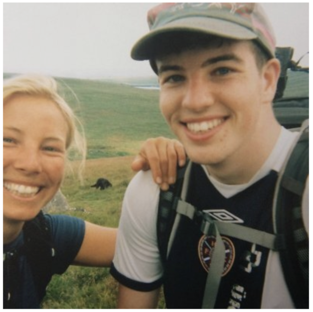 Blonde woman leans on the shoulder of a young man