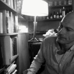 Bald man reviews books on a shelf