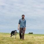Man walking with dog across field
