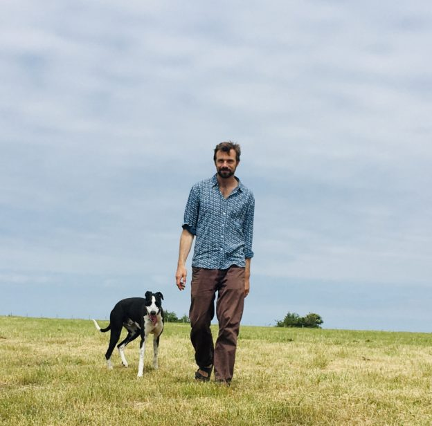 Man walking with dog across field